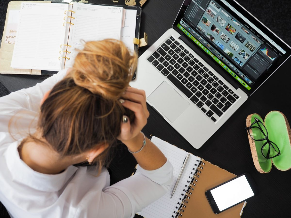 Woman with computer looking stressed